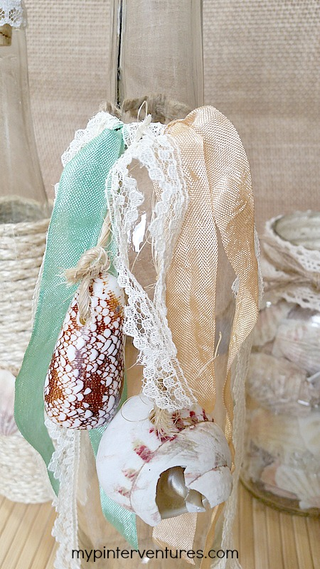 Ribbon and lace tied onto the seashell bottle