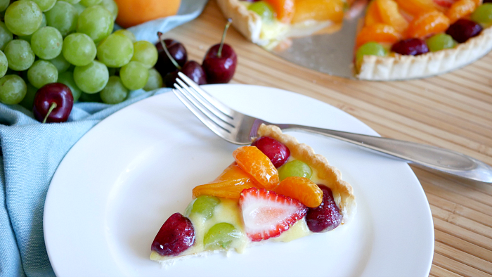Fresh fruit tart with orange curd slice on a plate