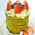 Stacked matcha pancakes with whipped cream and fresh fruits