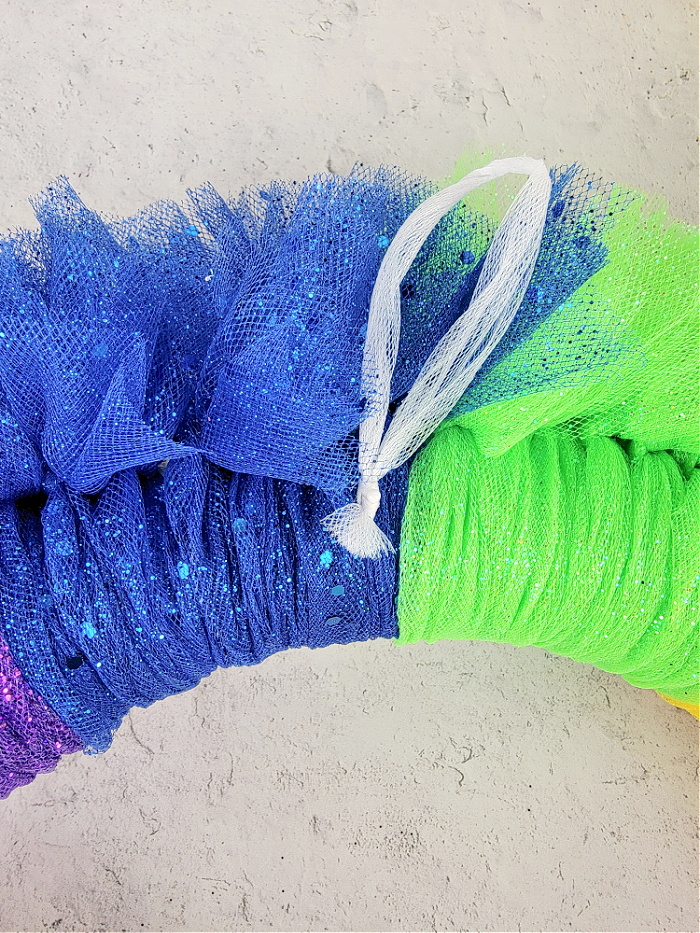 Attach hanging loop to spring tulle rainbow wreath
